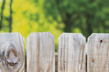 faded-wood-fence-planks-that-need-a-fence-repair-service