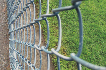 galvanized-chain-link-fencing-separating-grass-from-concrete